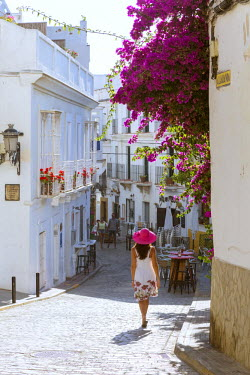 SPA5961AW Spain, Andalusia, Cadiz province, Tarifa. Woman walking in a street of the old town (MR)