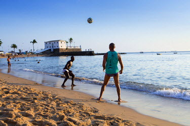 BRA2455AW South America, Brazil, Bahia, Salvador, Barra, locals playing football on Barra beach with the 17th Century Portuguese Santa Maria fort behind