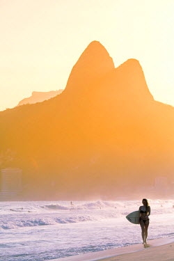 BRA2476AW South America, Brazil, Rio de Janeiro, Ipanema, a young woman carrying a surf board along the beach MR