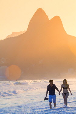 BRA2482AW South America, Brazil, Rio de Janeiro, Ipanema, a young couple walking hand in hand along the beach at sunset MR