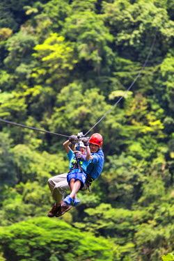 CR32982AW Costa Rica, Alajuela, La Fortuna, Arenal Volcano National Park. A child and guide zip lining at Sky Trek.