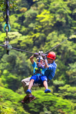CR32983AW Costa Rica, Alajuela, La Fortuna, Arenal Volcano National Park. A child and guide zip lining at Sky Trek.