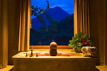 CR32993AW Costa Rica, Alajuela, La Fortuna. A lady looks out at the Arenal Volcano from a suite in the The Springs Resort and Spa. (MR).
