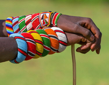 KEN8951 Kenya, Samburu County, Bawa. A Samburu warrior with beaded bracelets rests his hands on a walking stick.