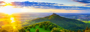 DE05216 Elevated view towards Hohenzollern Castle and sourrounding countryside illuminated at sunset, Swabia, Baden Wuerttemberg, Germany