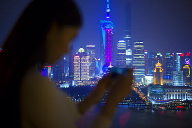 CN03436 Woman taking photos with smartphone infornt of the Pudong skyline, Shanghai, China (MR)
