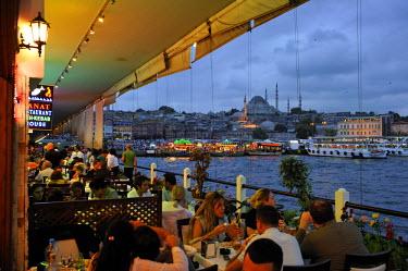 HMS0531104 Turkey, Istanbul, Eminonu District, restaurants under the Galata Bridge over the Golden Horn Strait, in the background Suleymaniye Camii (Suleyman Mosque) built by architect Mimar Sinan