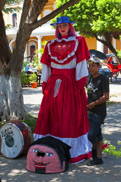 NIC0188 Nicaragua, Granada. La Gigantona. A 3m high doll used in street dances, representing the tall white Spanish women that arrived with the conquistadors. In front is the head of El Enano Cabezon, a small...