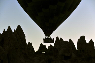 HMS0543843 Turkey, Central Anatolia, Nevsehir Province, Cappadocia listed as World Heritage by UNESCO, hot air baloon flying over an eroded landscape and fairy chimneys near Goreme