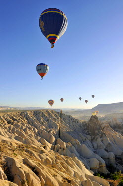 HMS0543847 Turkey, Central Anatolia, Nevsehir Province, Cappadocia listed as World Heritage by UNESCO, hot air baloon flying over an eroded landscape and fairy chimneys near Goreme