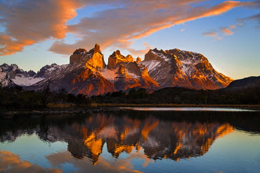 CHI8975 Chile, Torres del Paine, Magallanes Province. Sunrise over Torres del Paine reflected in the waters of Lake Pehoe in the foreground. One of the principal attractions of the National Park is the magnif...