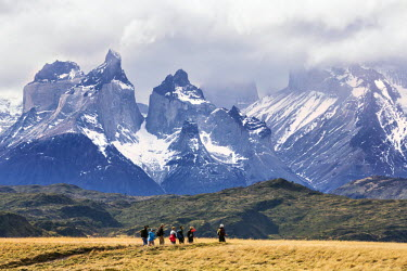 CHI8996 Chile, Torres del Paine, Magallanes Province. Hikers are dwarfed by the magnificent Paine Massif in the Torres del Paine National Park.