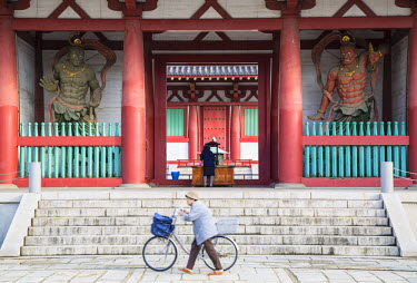 JAP0697AW Woman pushing bicycle past Shitenno-ji temple, Tennoji, Osaka, Kansai, Japan