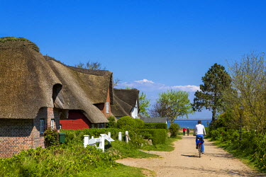 GER8263AW Thatched houses and cyclist, Nebel, Amrum Island, Northern Frisia, Schleswig-Holstein, Germany