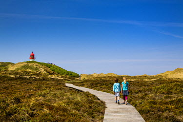GER8276AW Walker and lighthouse, Amrum Island, Northern Frisia, Schleswig-Holstein, Germany