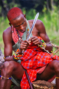 KEN9138AW Africa, Kenya, Narok County, Masai Mara. A Maasai man carving with a knife.