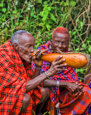 KEN9139AW Africa, Kenya, Narok County, Masai Mara. Masai elders dressed in traditional attire at their homestead, preparing for one of their customary ceremonies.