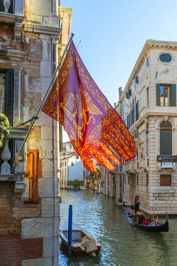 ITA3589AW Italy, Veneto, Venice. Gondola passing on a canal with venetian flag hanging from a wall