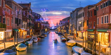 ITA3614AW Italy, Veneto, Venice, Murano island. Canal at sunset with Christmas lights hanging