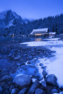 SLV1295AW Frozen lake shore and Mountain House at twilight, Popradske Pleso, High Tatras, Slovakia, Europe. Winter