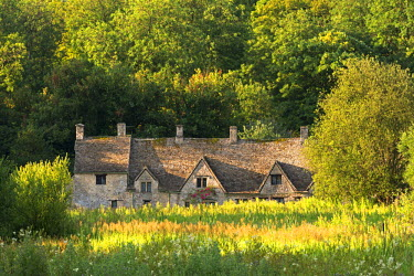 ENG11831AW Arlington Row cottages in the Cotswold village of Bibury, Gloucestershire, England. Summer (July)