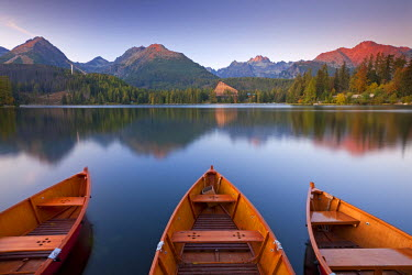 SLV1299AW Rowing boats and mountains beneath a twilight sky, Strbske Pleso Lake in the High Tatras, Slovakia, Europe. Autumn