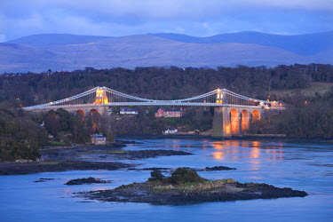 WAL7440AW The Menai Bridge spanning the Menai Strait, backed by the mountains of Snowdonia National Park, Wales, UK. Spring