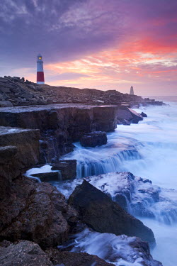 ENG12154AW Waves crash against the limestone ledges near the lighthouse at Portland Bill, Dorset, England. Winter