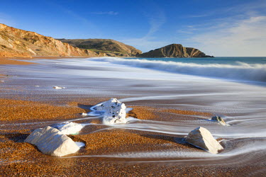 ENG12164AW Waves wash clean the beautiful beach at Worbarrow Bay on the Jurassic Coast, Dorset, England. Winter