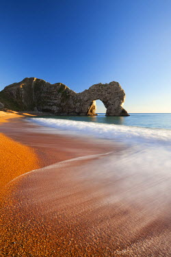 ENG12176AW Waves break onto Durdle Door beach, Jurassic Coast, Dorset, England. Winter