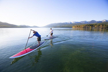 ARMOCR000217 A fit male and female paddle their stand up paddle boards (SUP) at sunset on Whitefish Lake in Whitefish, Montana. USA