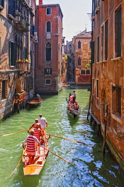 ITA3873 Local gondaliers row their traditional boat in one of Cannaregios canals, Cannaregio, Venice, Veneto, Italy.