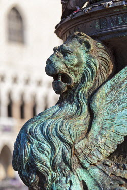 ITA3881 Architectural detail of a winged lion on the base of a lamp post in Piazza San Marco, with the Doge's Palace in the background, Piazza San Marco, Venice, Veneto, Italy.