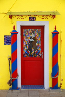 ITA3892 Colourful, Ornate traditional doorway and striped mooring posts in the town of Burano, Venice, Veneto, Italy.