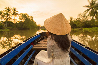 VIT0734AW Woman wearing ao dai dress in boat at dawn, Can Tho, Mekong Delta, Vietnam (MR)
