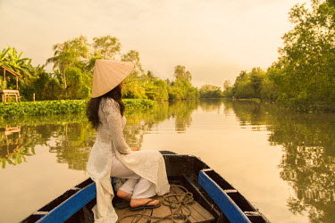 VIT0735AW Woman wearing ao dai dress in boat, Can Tho, Mekong Delta, Vietnam (MR)