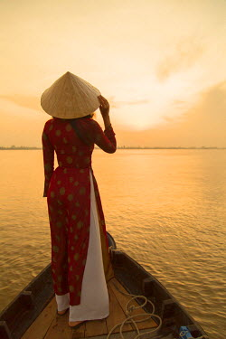 VIT0743AW Woman wearing ao dai dress in boat at dawn, Can Tho, Mekong Delta, Vietnam (MR)