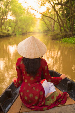 VIT0745AW Woman wearing ao dai dress in boat, Can Tho, Mekong Delta, Vietnam (MR)