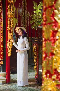 VIT0767AW Woman wearing ao dai dress at Phuoc An Hoi Quan Pagoda, Cholon, Ho Chi Minh City, Vietnam (MR)