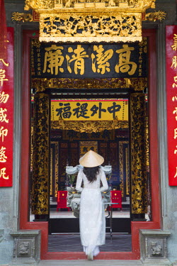 VIT0771AW Woman wearing ao dai dress at Nghia An Hoi Quan Pagoda, Cholon, Ho Chi Minh City, Vietnam (MR)