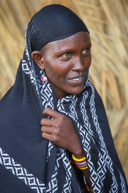 KEN9224 Kenya, Marsabit County, Kalacha.  A Gabbra woman outside her house.