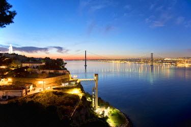 POR8204AW Lisbon and 25 de Abril bridge over the Tagus river, at dusk, seen from Almada. Portugal