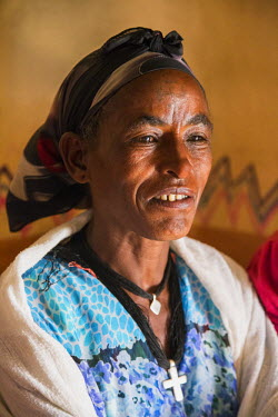 ETH2613 Ethiopia, Gheralta, Tigray Region. A Tigray woman in her home.  The people are deeply religious Coptic Christians and often have crosses tattooed on their foreheads like this woman.