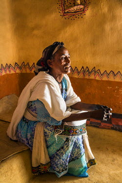 ETH2614 Ethiopia, Gheralta, Tigray Region. A Tigray woman in her neat home.  The people are deeply religious Coptic Christians and often have crosses tattooed on their foreheads like this woman.