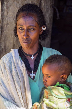 ETH2615 Ethiopia, Gheralta, Tigray Region. A Tigray woman and her son.  Her hairstyle is typical of the region. The people are deeply religious and often have crosses tattooed on their foreheads like this wom...