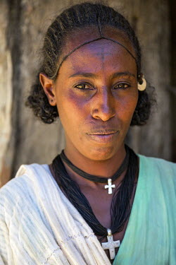 ETH2616 Ethiopia, Gheralta, Tigray Region. A Tigray woman at the entrance to her home.  Her hairstyle is typical of the region. The people are deeply religious and often have crosses tattooed on their forehea...