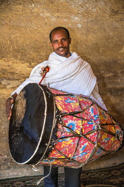 ETH2619 Ethiopia, Wukro, Tigray Region. A large ceremonial drum with an attendant inside the crooked cruciform semi-monolithic church of Wukro Cherkos.