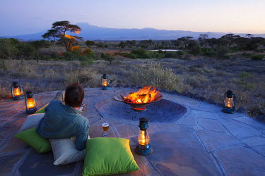 KEN9344 Kenya, Amboseli National Park, Tortilis Camp. A guest relaxes with a beer, overlooking Mount Kilimanjaro. MR.