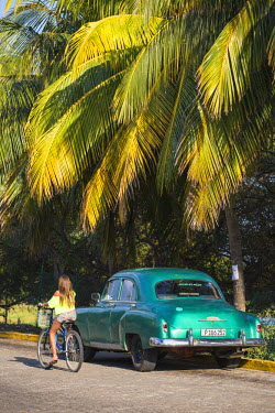 CB02410 Cuba, Varadero, Girl cycling past Classic vintage American car