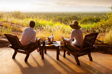 KEN9401 Kenya, Meru National Park, Elsa's Kopje. A couple enjoy an evening drink overlooking Meru National Park. MR.